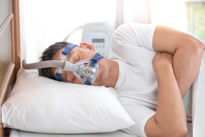 man sleeping in bed wearing cpap mask ,sleep apnea therapy happy and healthy senior man sleeping deeply on his left side without snoring