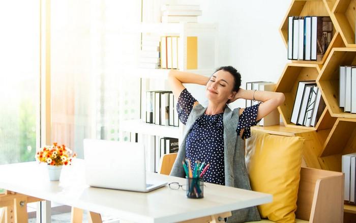 home offic eeinrichten schreibtisch home office büro mit laptop frau am büro entspannt standregalen hinten