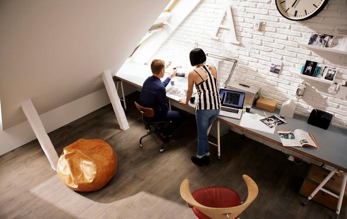 home office ausstattung am dachboden büro zuhause langer schreibtisch vor dem wand ziegelwand in weiß mann und frau arbeiten