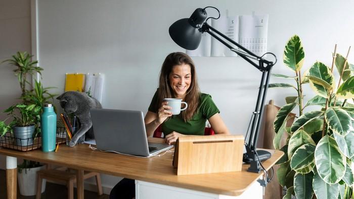 home office einrichten büro ideen für arbeitsplatz zuhause home office ideen frau am büro mit kafeetasse lächelt große pflanzen