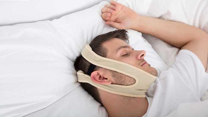 informationen und tipps was kann man gegen schnarchen machen mann schläft mit einem band am kopf gegen schnarchen
