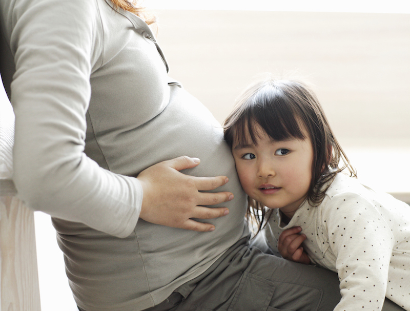 little girl listening to pregnant mother's abdomen