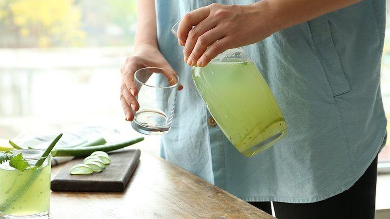 mann gießt aloe vera saft in einem glas