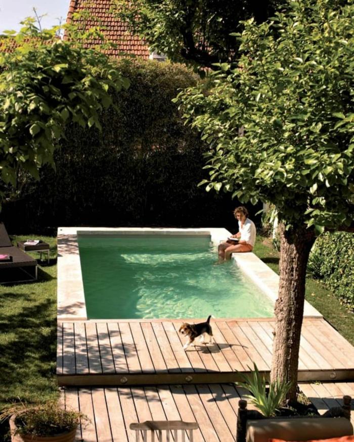 mann sitz mit füßen im schwimmbad kleiner hund pool für kleinen garten grüne bäume und pflanzen