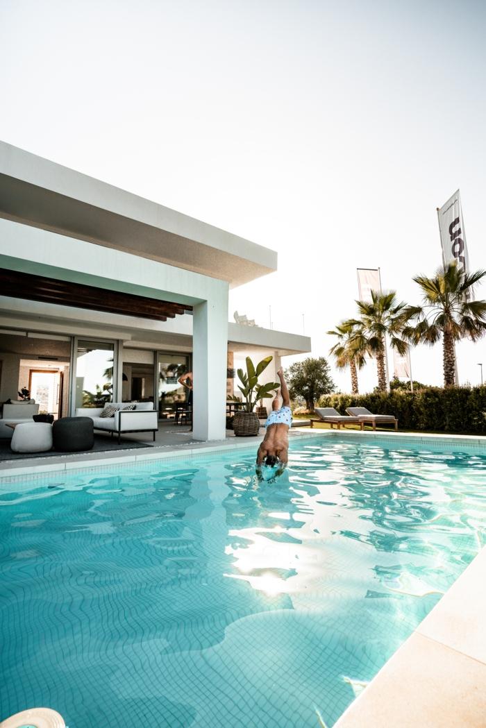 mann springt in einem schwimmbad großer swimming pool garten großes haus garten einrichten ideen