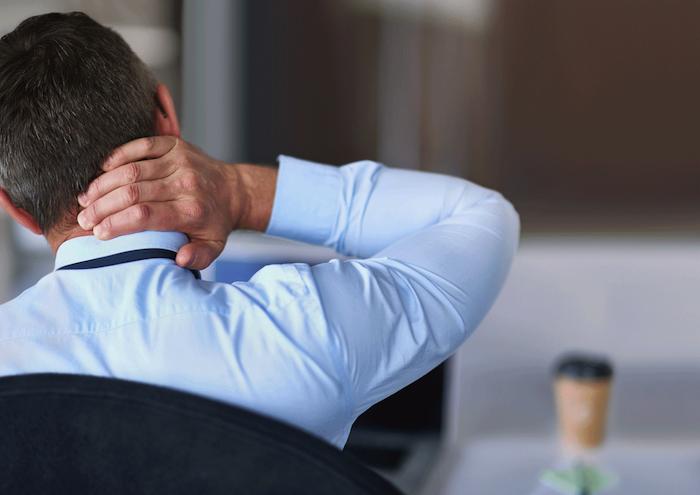 nackenschmerzen bekämpfen mann sitzt auf einem stuhl im büro trainiren mit muskelkater