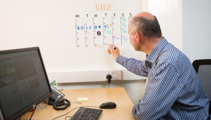 schreibtisch einrichten home office büro ideen büro einrichtungsideen mann am büro computer schreibt whiteboard agenda