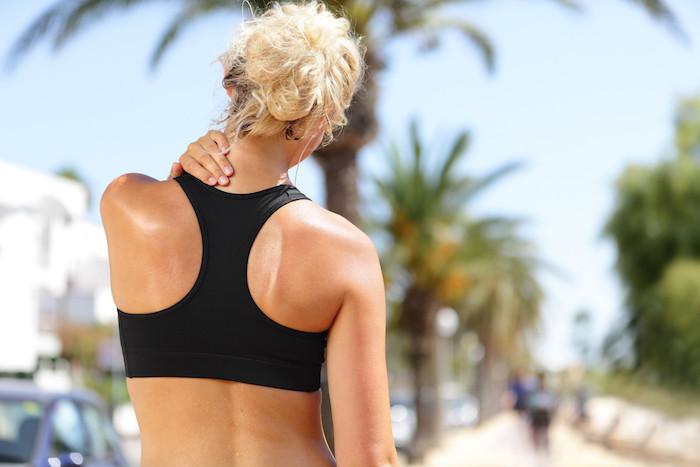 sport treiben drausen frau geht joggen schmerzen im nacken trainiren mit muskelkater sportliche bekleidung schwarzer sportlicher bh