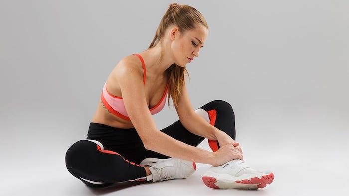 sportliches outfit schwarze leggins pinker sport bh frau mit hochgesteckten haaren muskelkater loswerden