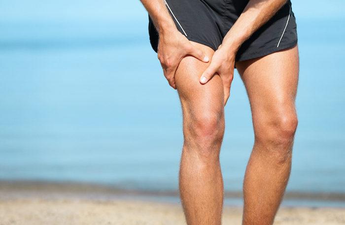 training-am-stran-person-mit-schmerzen-im-bein-sport-trotz-muskelkater-kurze-schwarze-sporthose