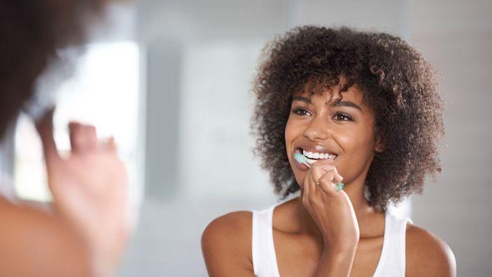 was kann man gegen zahnschmerzen machen zahnfleischentzündung was tun entzündung im mund hausmittel zähne regelmäßig putzen frau mit lockigen haaren vor dem spiegel wäscht scih die zähne