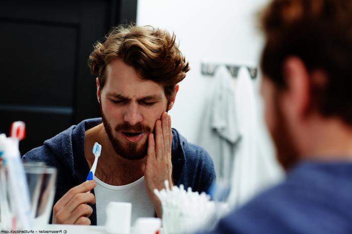 was kann man gegen zahnschmerzen machen zahnschmerzen hausmittel zahnfleischentzündung kind entzündung im mund hausmittel mann im badezimmer wascht die zähne hält den mund zahnschmerzen