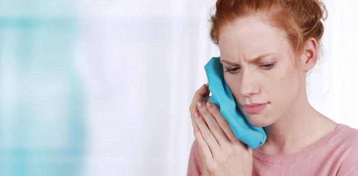 was tun bei zahnschmerzen schmerzmittel bei zahnschmerzen entzündung im mund kalter tuch gegen zahnschmerzen frau mit blauem tuch auf den kiefer