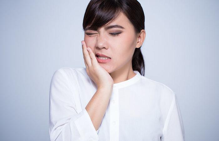 zahnschmerzen was tun zahnschmerzen lindern entzündungshemmende hausmittel zahnfleischschmerzen junge frau leidet an zahnschmerzen