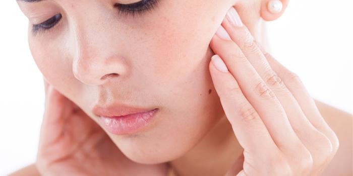 zahnwurzelentzündung selbst heilen hausmittel gegen zahnschmerzen karies selbst behandeln kieferentzündung junge frau mit zahnschmerzen hält den mund
