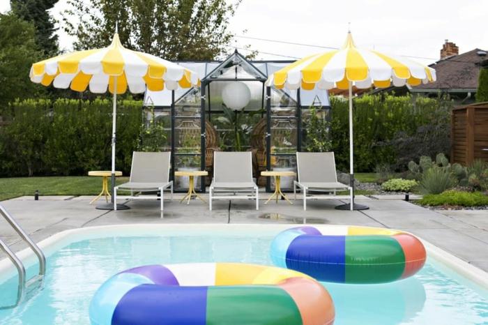 zwei große bunte rettungsringe schirme in gelb und weiß drei chaiselongues swimming pool garten inspiration und ideen