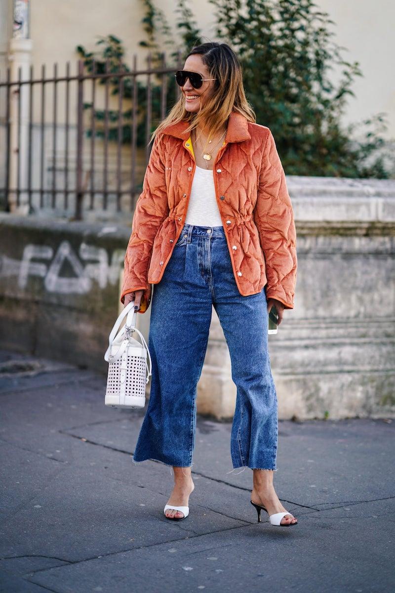 weite hose welche schuhe wide leg jeans kombinieren junge frau in blauen wide leg jeans und roter jacke