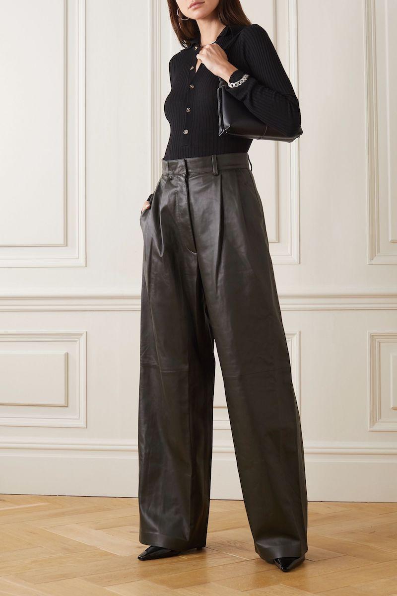 wide leg jeans kombineren lederhose mit schwarzer bluse junge frau im raum