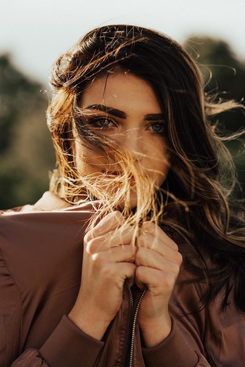braune haare mit highlights frau mit langen haaren und brauner jacke portrait im freien
