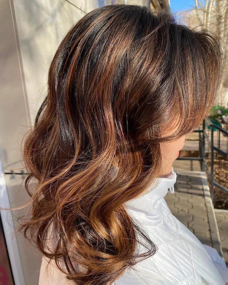 braune haare mit strähnen frau mittlellange dunkelbraun mit caramel frisur im freien