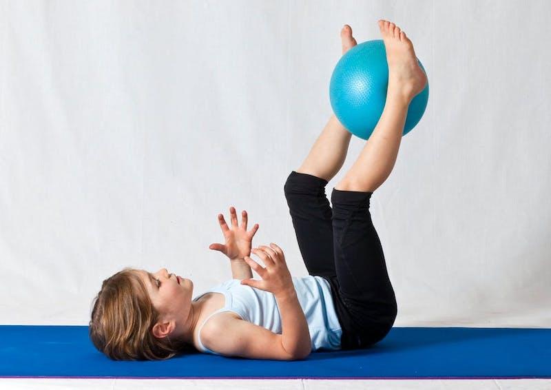 gymnastikübungen für kinder ein mädchen mit blauen ball zwischen beinen auf blauer matte