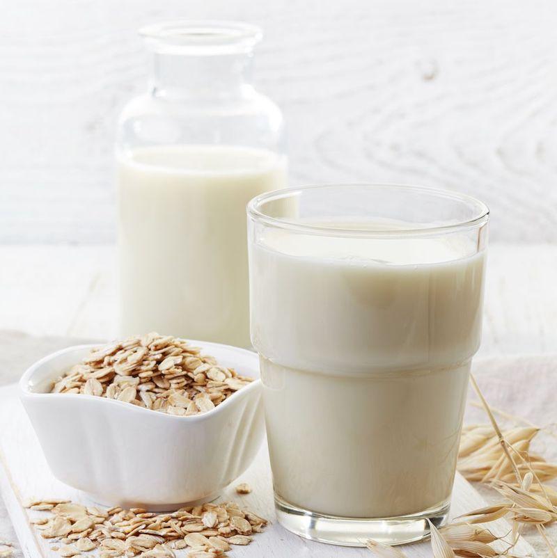 hafermilch haltbar machen hafermilch in glasflasche glas und raue haferflocken in schüssel