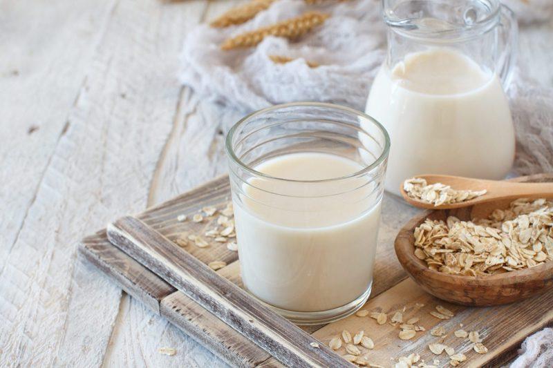 hafermilch ohne zucker hafermilch in glasgefäß und in glas auf holztafel