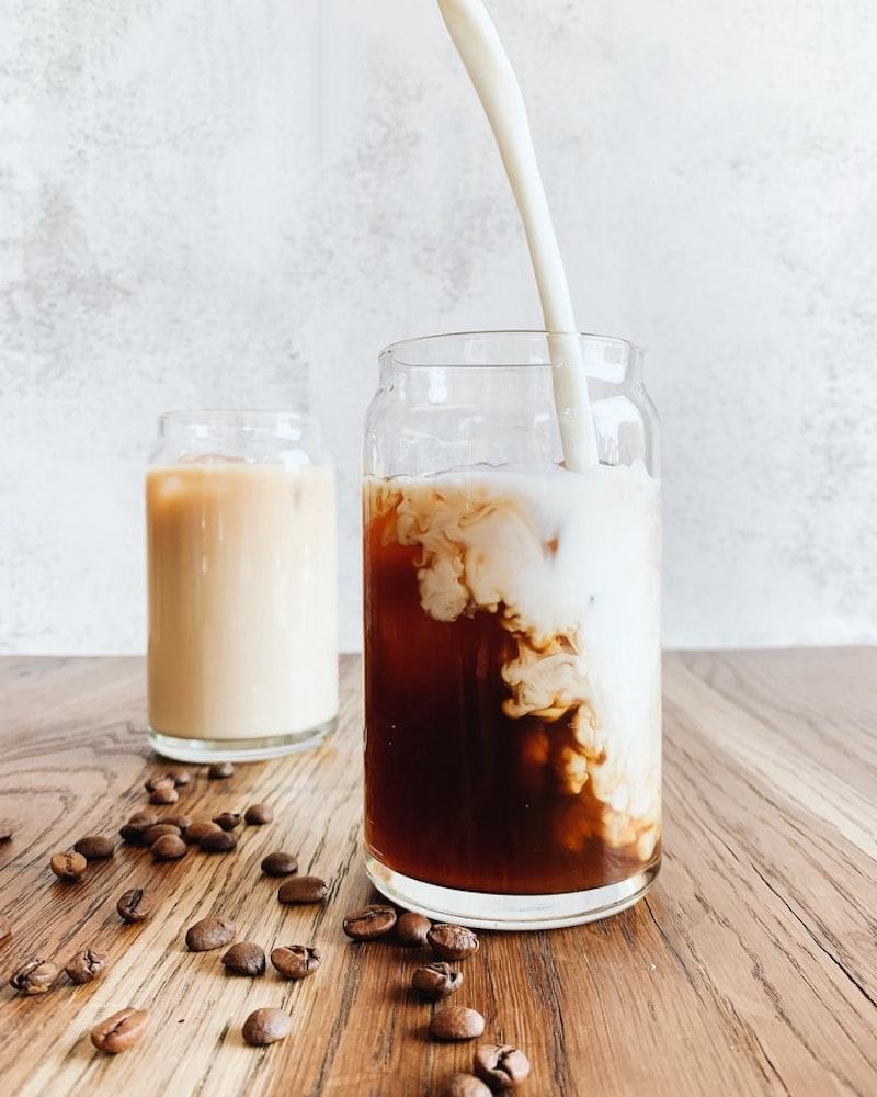 hafermilch zuckerfrei kaffee mit hafermilch in einer glasstasse ausgießen kaffeebohnen auf dem tisch