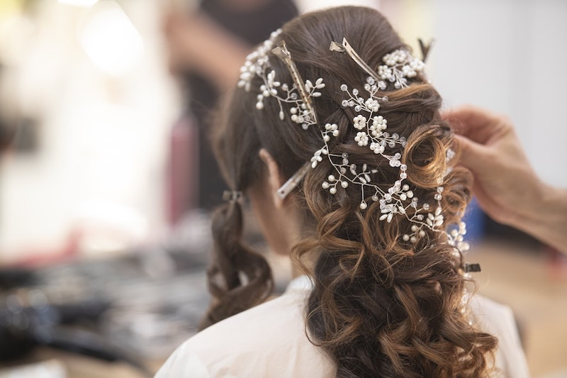 highlights braune haare hochzeitfrisur mit fauxblumen eine frau beim friseur
