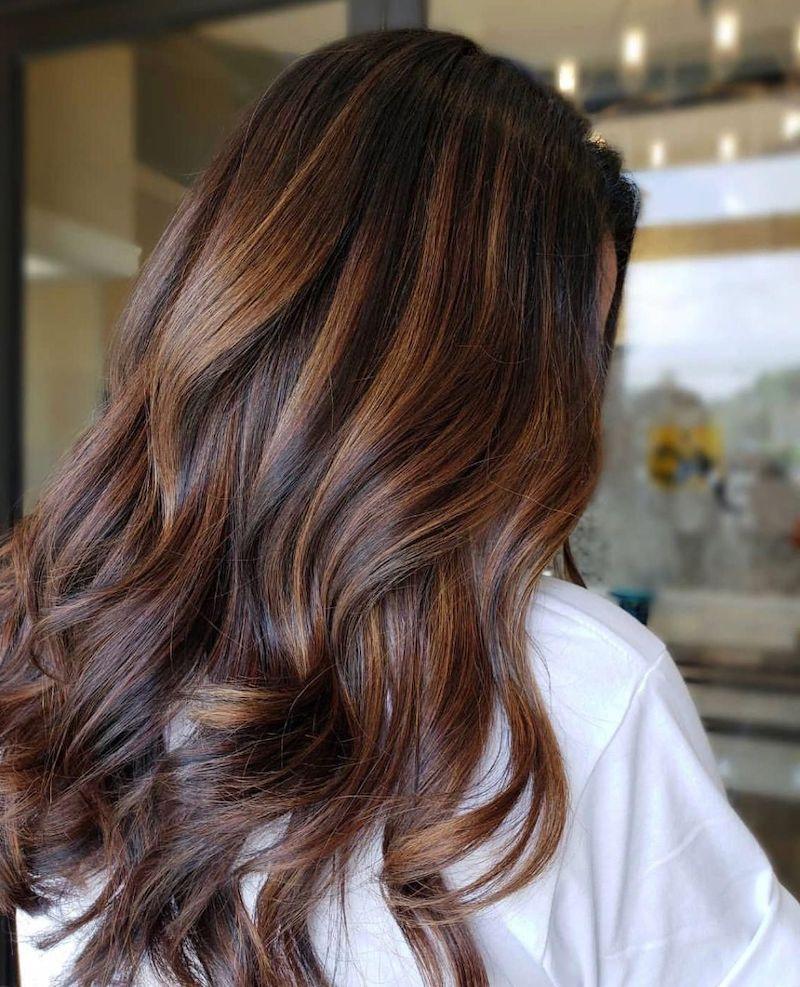 kastanienbraun haarfarbe mit karamell strähnen eine frau beim friseur
