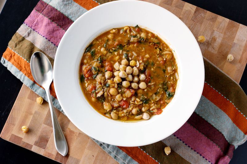 kichererbsensuppe mit spinat im weißer schüssel mit silberlöffel essen