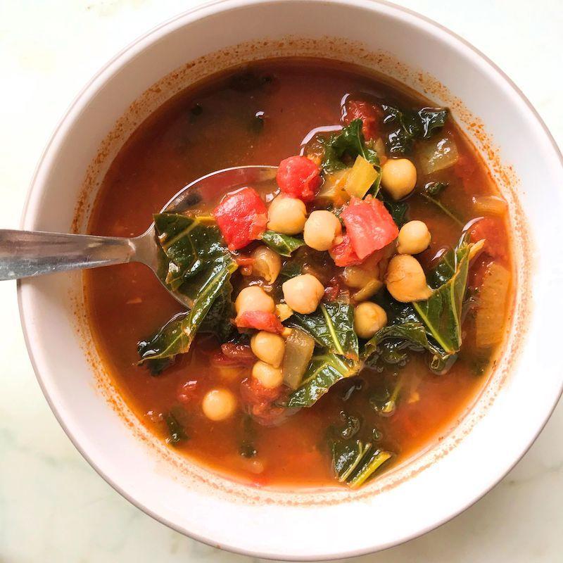 kichererbsensuppe mit spinat und tomaten in einer weißen schüssel