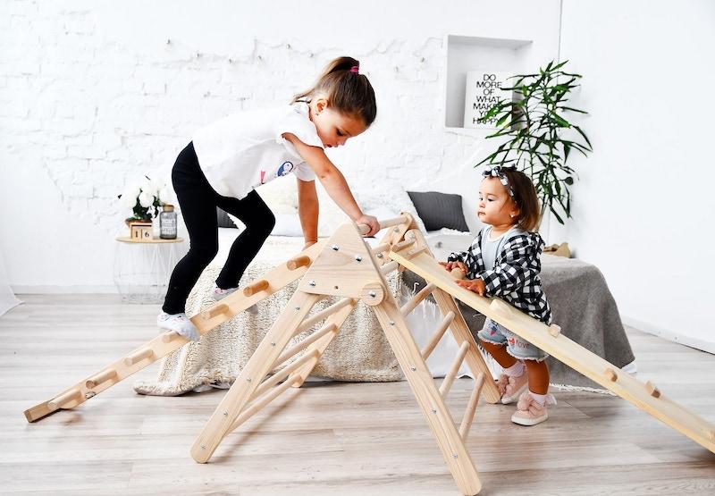 lustige partnerübungen sport zwei mädchen schwestern klettern sich auf indoor spielgerät