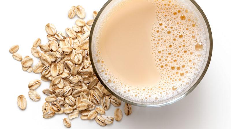 rezepte mit hafermilch getreidemilch in glas mit haferflocken daneben auf weißem tisch