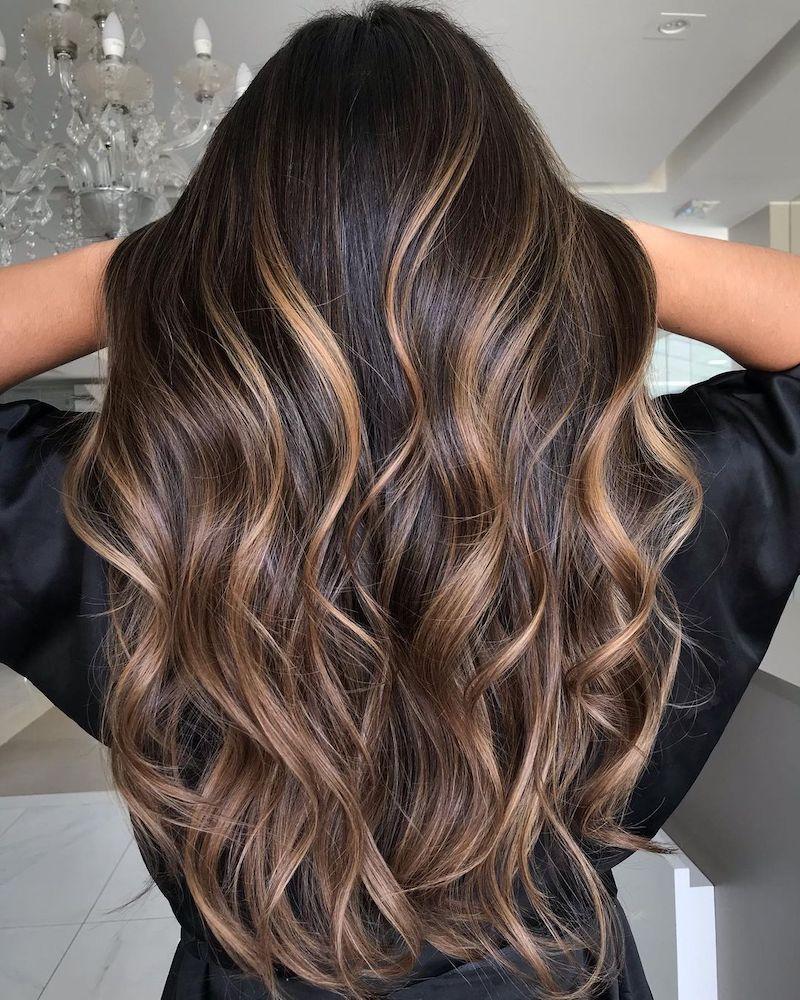 schwarze haare mit strähnen eine frau hebt ihr haar mit händen