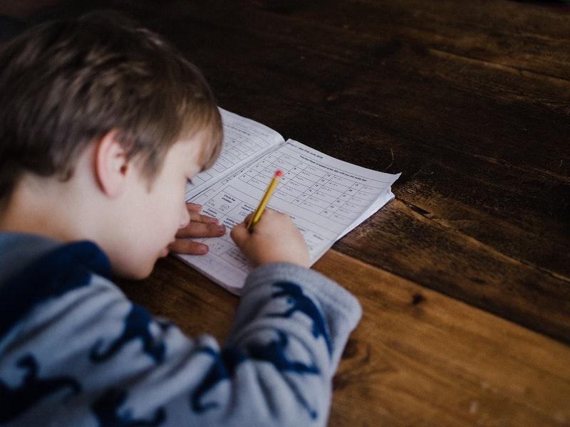 sport für kinder zu hause ein junge schreibt ins heft auf dem schreibtisch