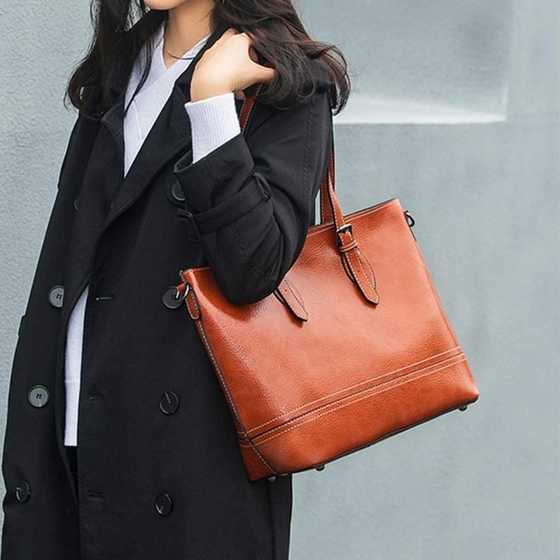trendfarben herbst winter 2021 2022 frau in trenchcoat schwarz mit shopping schultertasche