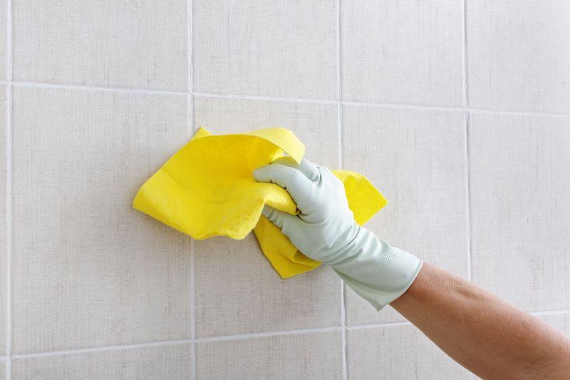 wandfliesen verfugen weiße wandfliesen mit gelbem lappen waschen