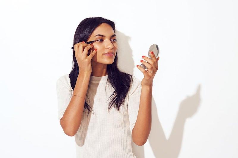 weißer eyeliner eyeliner hacks auftragen frau mit spiegel trägt eyeliner auf