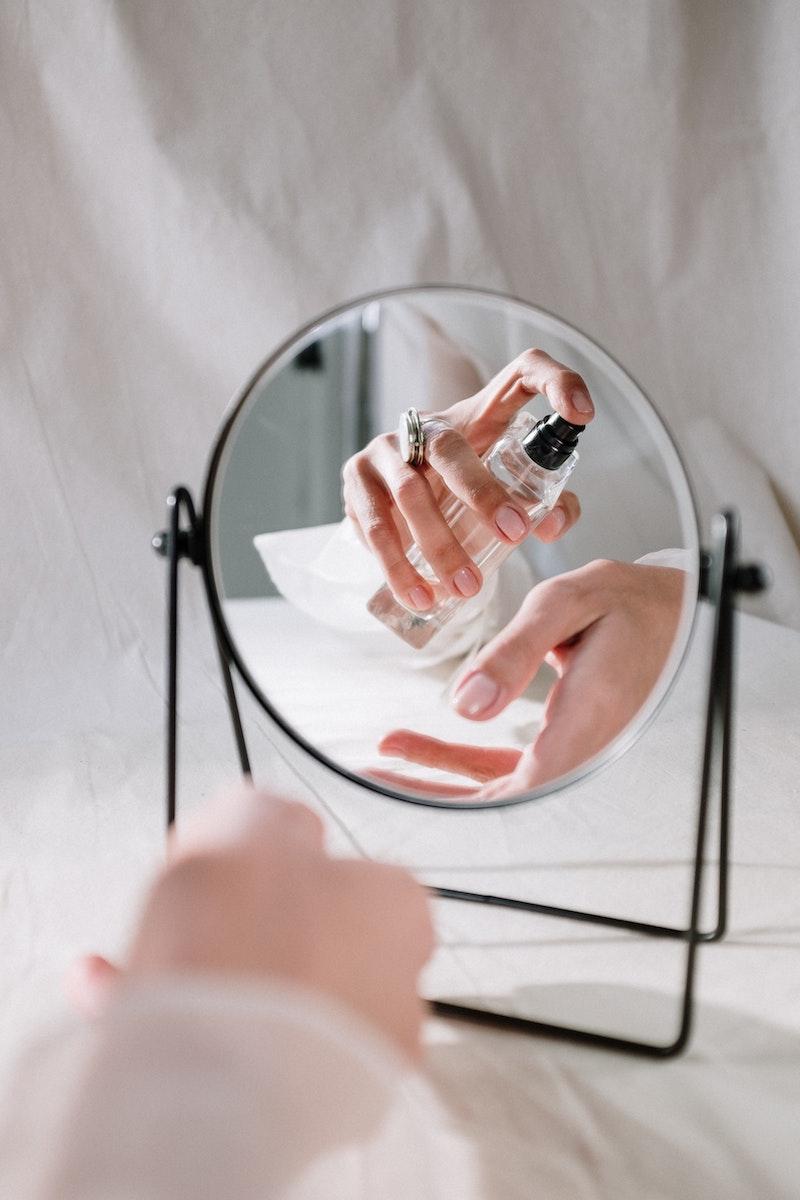 wo sprüht man parfum hin teures parfum parfum auftragen frau vor spiegel handgelenk besprühen
