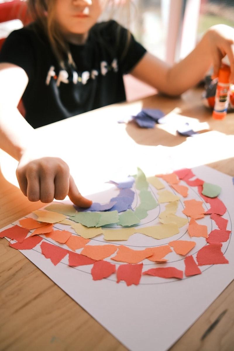 basteltipps für kinder ein mädchen klebt regenbogen aus papier