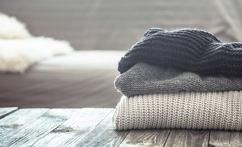 a stack of knitted sweaters on a wooden table