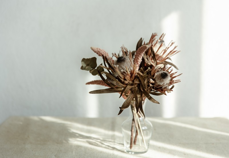 arrangement of dried flowers in a glass vase close up.
