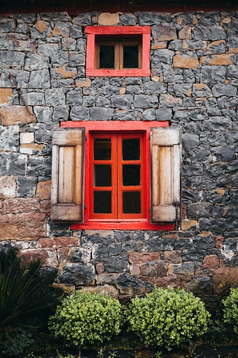 fassade mit spülmittel reinigen steinhaus mit roten fenstern