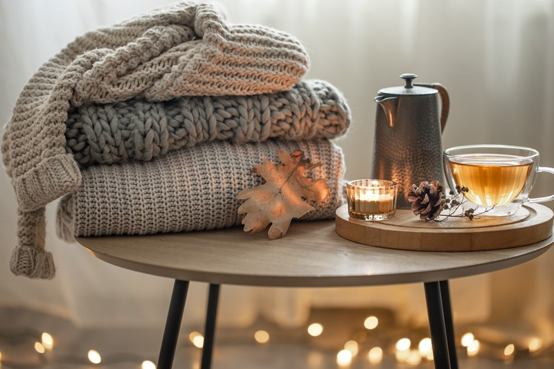 cozy autumn composition with a cup of tea and a stack of knitted sweaters.