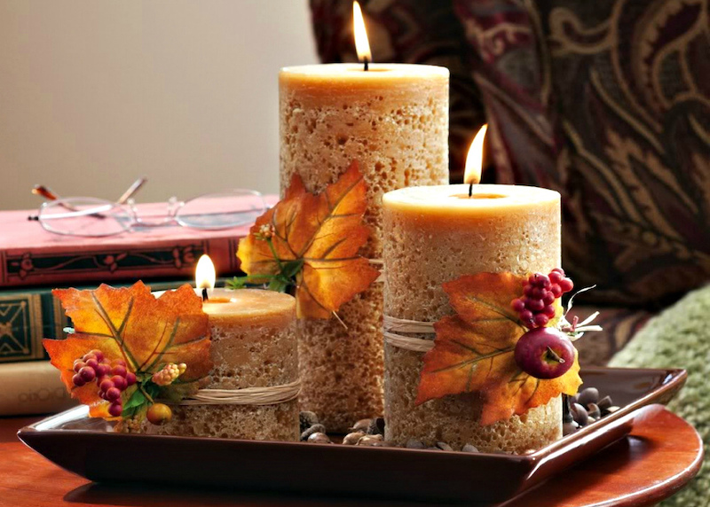herbstdeko für den tisch mit rotem weinlaub und kerzen orangenfarbe