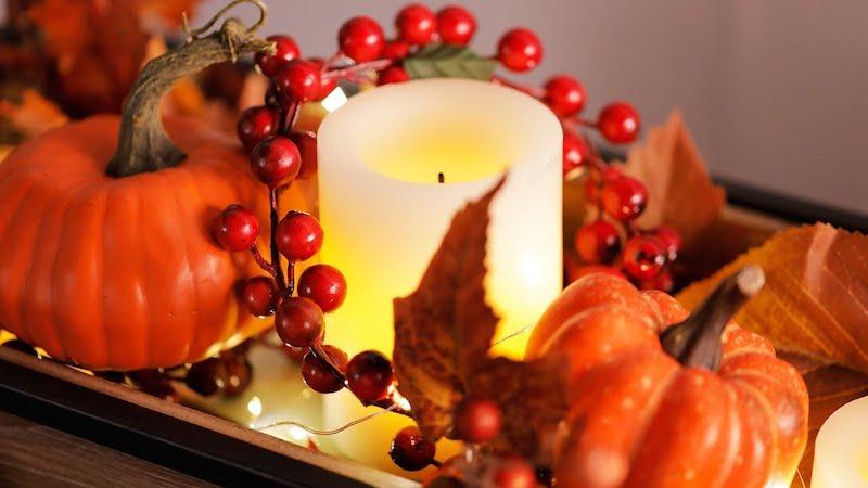herbstdeko für den tisch mit rotem weinlaub und kerzen
