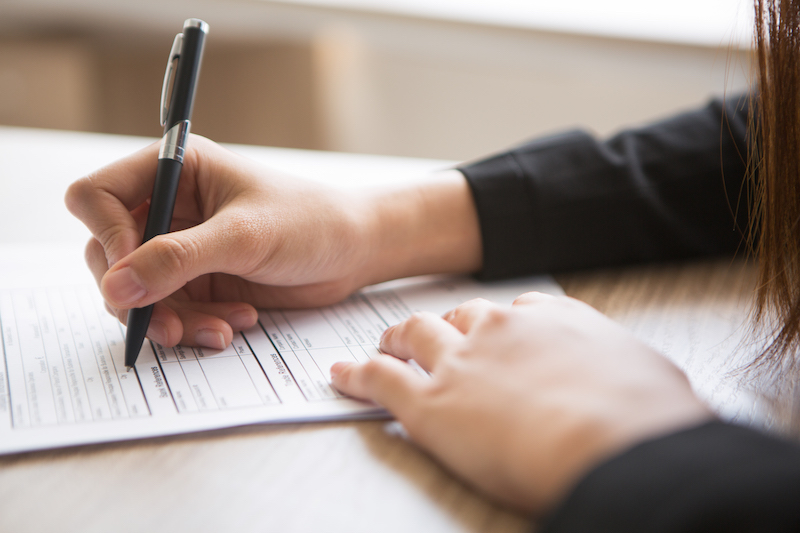 cropped view of woman filling in application form